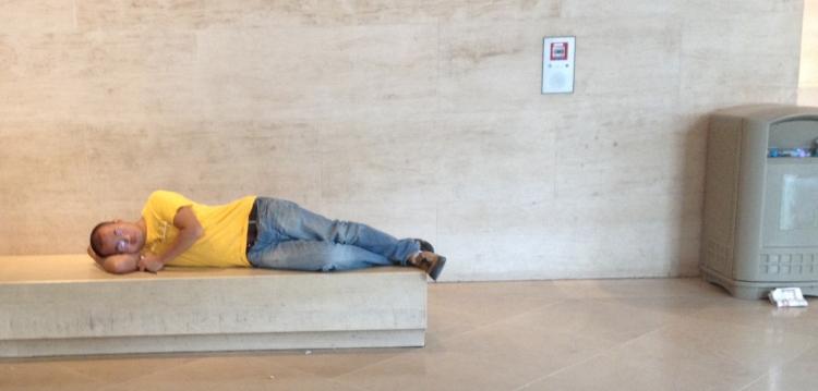 Homme allongé sur un banc de pierre, mezzanine du hall Napoléon, Musée du Louvre, 05/12/14